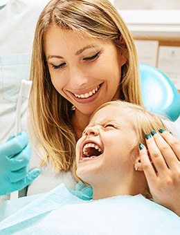 Mother and daughter in exam chair for children's dentistry checkup