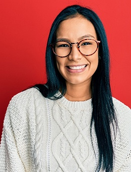 A young woman wearing a cream sweater and glasses smiles after receiving her dental crowns