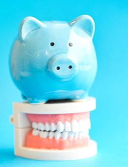 blue piggy bank sitting on top of set of artificial teeth