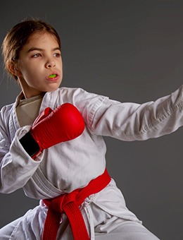 A little girl wears a white robe, red belt, and red boxing gloves while sporting a mouthguard to protect her smile
