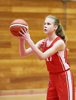 A teenage girl attempts a free throw while wearing a mouthguard