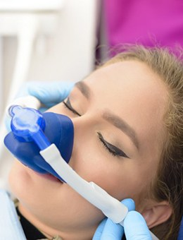 Young woman wearing mask for nitrous oxide sedation dentistry in Murphy