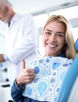 Woman giving thumbs up in dental chair after nitrous oxide sedation dentistry visit