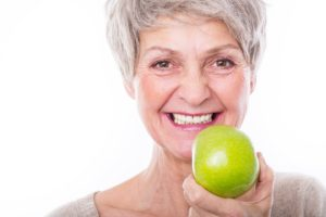 smiling senior woman holding apple