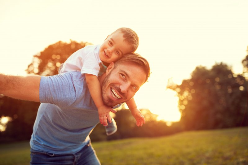 father smiling and playing outside with son